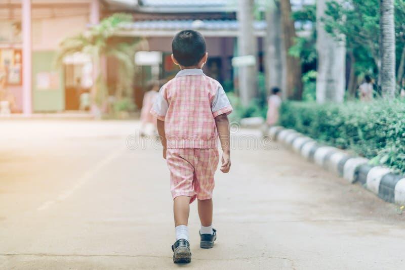 后面观点的男孩跟随在街道上的女友去教室 免版税库存图片