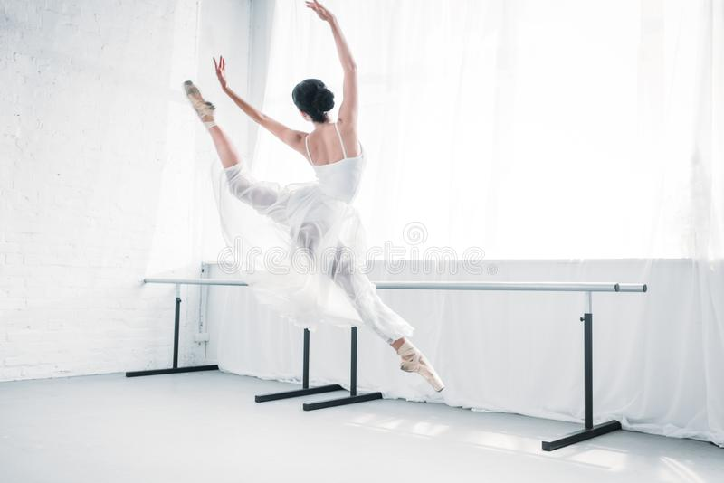 后面观点的白色礼服跳舞的优美的年轻芭蕾舞女演员在芭蕾演播室 免版税库存照片
