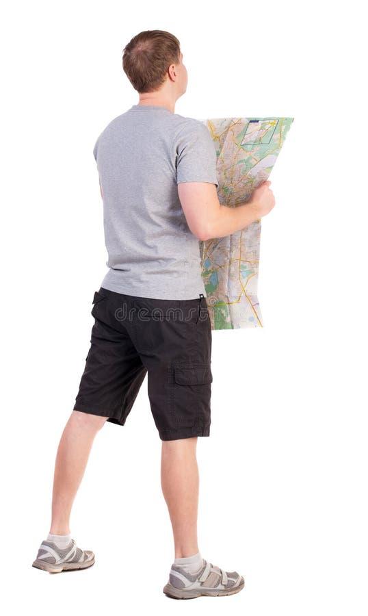 后面观点的看地图的旅途年轻人 库存照片
