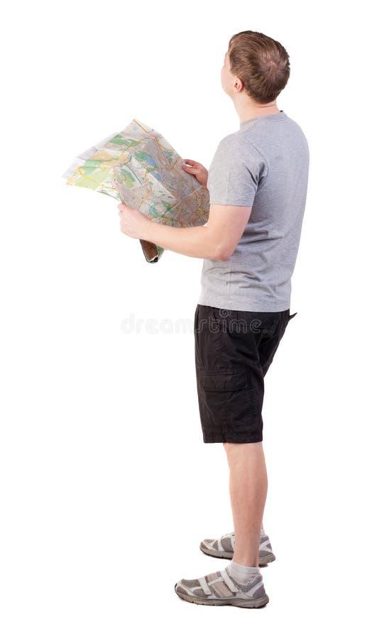 后面观点的看地图的旅途年轻人 免版税库存图片
