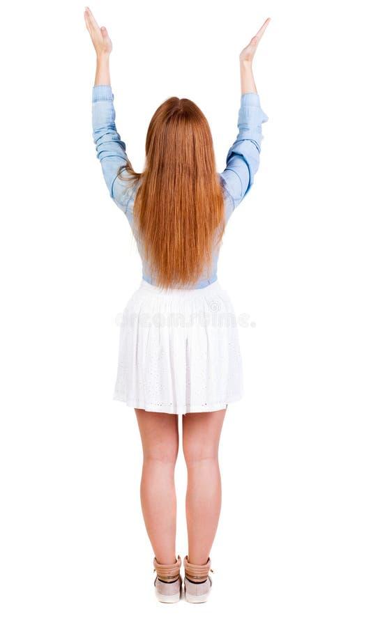 后面观点的看墙壁和举行的礼服的美丽的妇女 免版税库存照片
