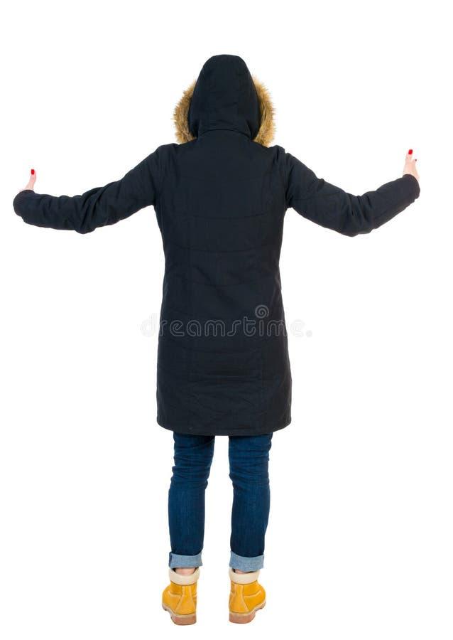 后面观点的看墙壁和举行的附头巾皮外衣的美丽的妇女 免版税库存照片
