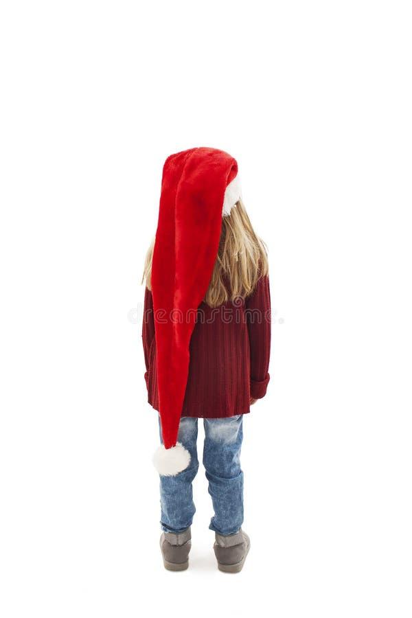 后面观点的看墙壁的红色圣诞老人帽子的女孩 o 图库摄影