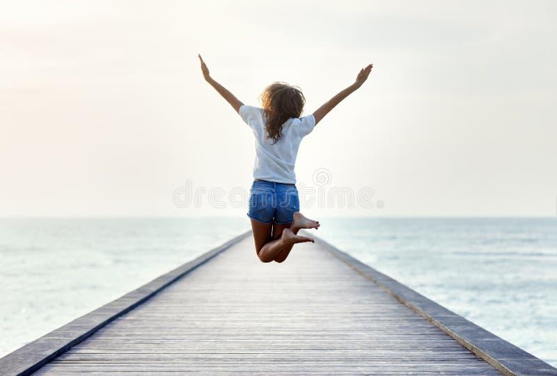 后面观点的码头的跳跃的女孩 库存图片