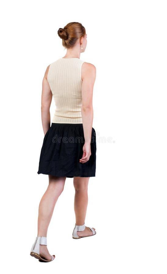 后面观点的礼服的走的妇女 m的美丽的白肤金发的女孩 免版税图库摄影