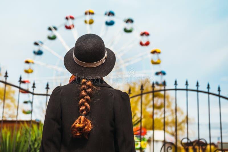 后面观点的站立在弗累斯大转轮前面的帽子的一个女孩在游乐园 免版税库存照片