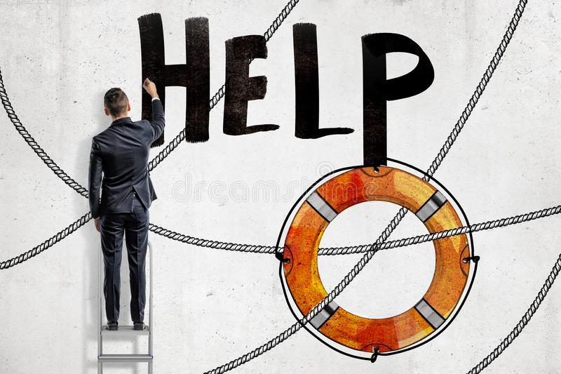 后面观点的站立在梯子和写标题'帮助的'衣服的一个人在有绘画的墙壁上lifebuoy 图库摄影