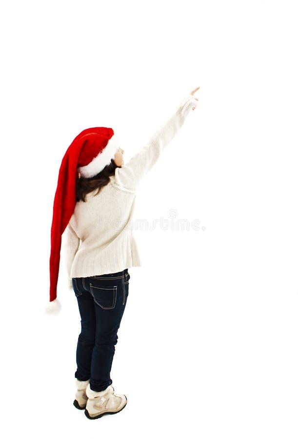 后面观点的红色圣诞老人帽子的小女孩指向墙壁 库存照片