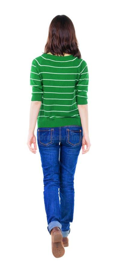 后面观点的红色毛线衣的走的妇女 免版税库存照片