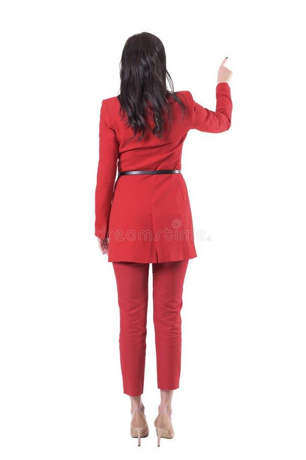 后面观点的红色衣服的典雅的女商人使用屏幕 免版税图库摄影
