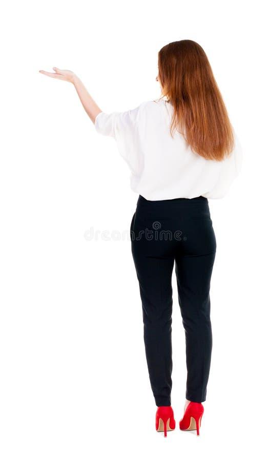 后面观点的美丽的女商人在看墙壁的随员和举行递  库存照片