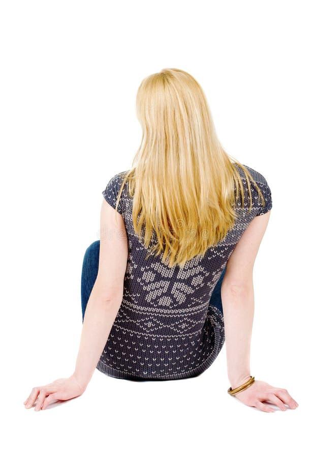 后面观点的美丽的少妇坐地板 图库摄影