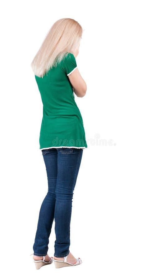 后面观点的蓝色牛仔裤的震惊妇女 图库摄影