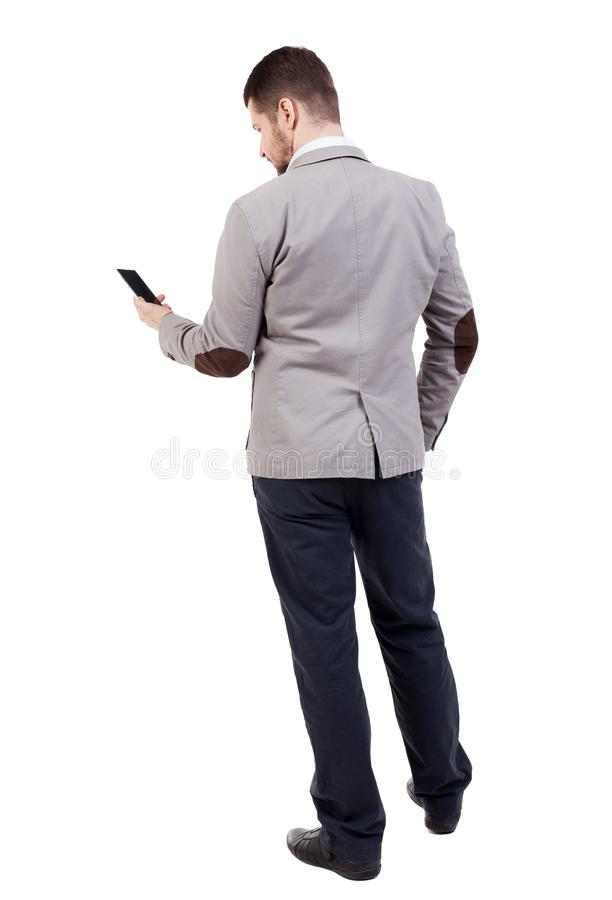 后面观点的衣服的商人谈话在手机 免版税库存照片