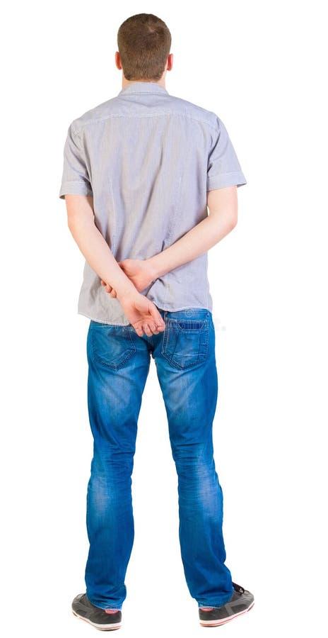 后面观点的衬衣和牛仔裤的年轻人。 免版税库存照片