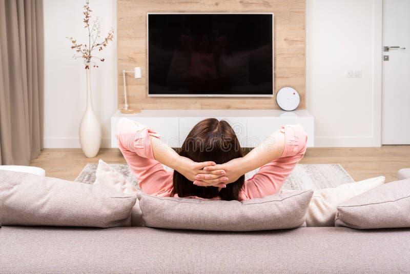 后面观点的豪华公寓的孤独的哀伤的压抑美丽的年轻女人,坐沙发和看着电视 库存图片
