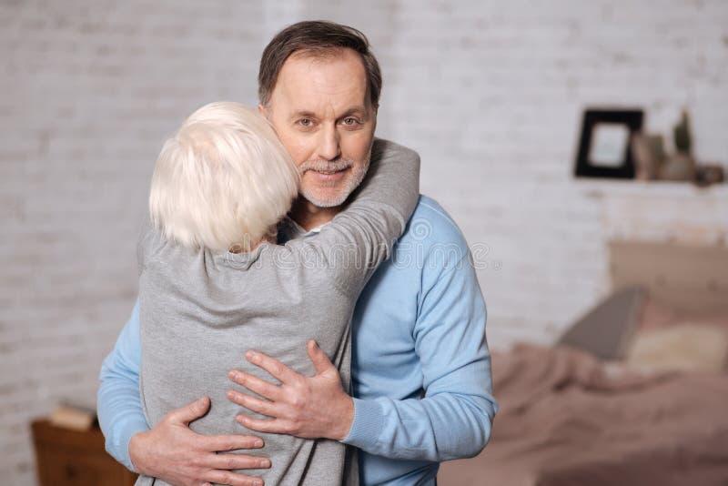 后面观点的资深妇女拥抱的丈夫 免版税库存图片