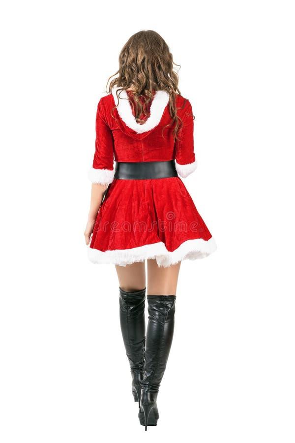后面观点的走开红色圣诞节的礼服的女性圣诞老人 免版税库存照片