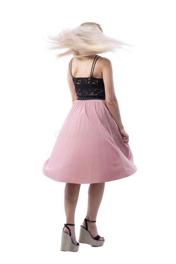 后面观点的转动和跳舞与飞行的头发的夏天裙子的白肤金发的年轻女人 免版税库存照片
