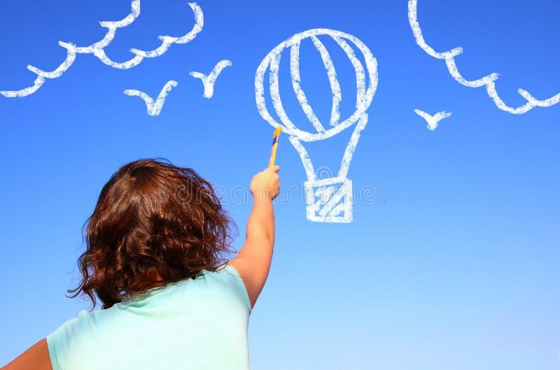 后面观点的逗人喜爱的孩子想象和绘画在天空的空气baloon 库存照片