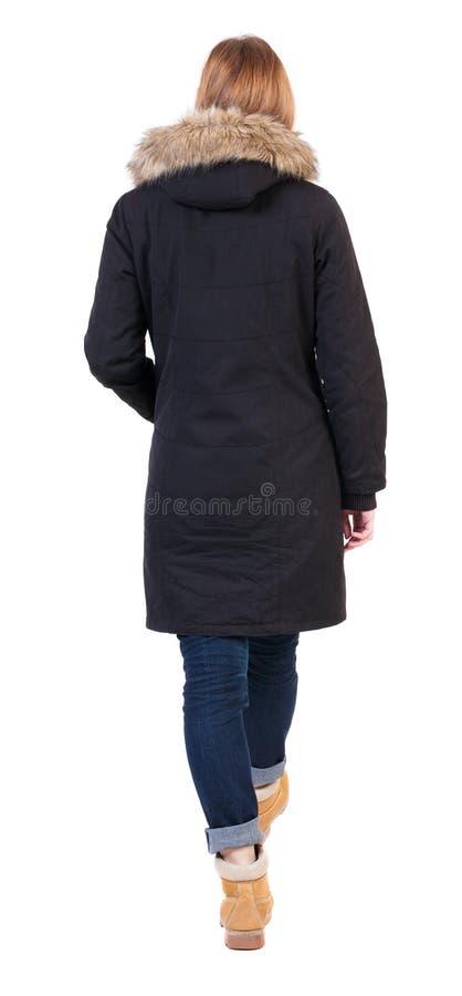 后面观点的附头巾皮外衣的去的妇女 免版税图库摄影