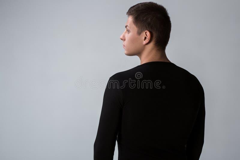 后面观点的黑毛线衣的人 常设年轻人 查出的背面图白色 免版税库存图片