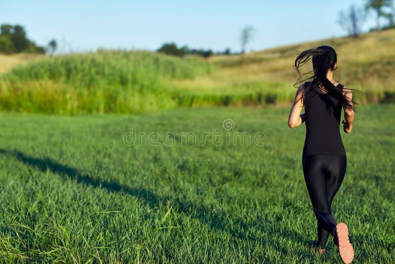 后面观点的黑运动服赛跑的妇女 免版税图库摄影