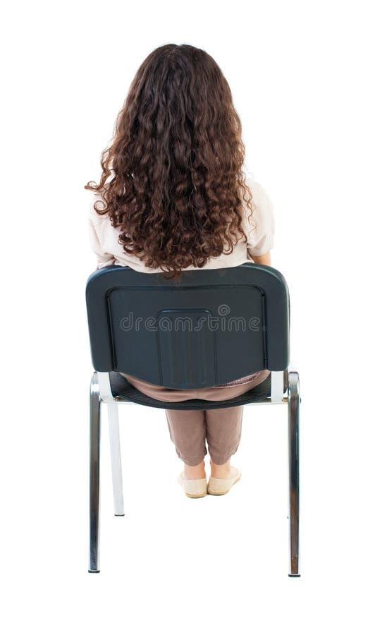 后面观点的年轻美丽的妇女坐椅子 免版税库存图片