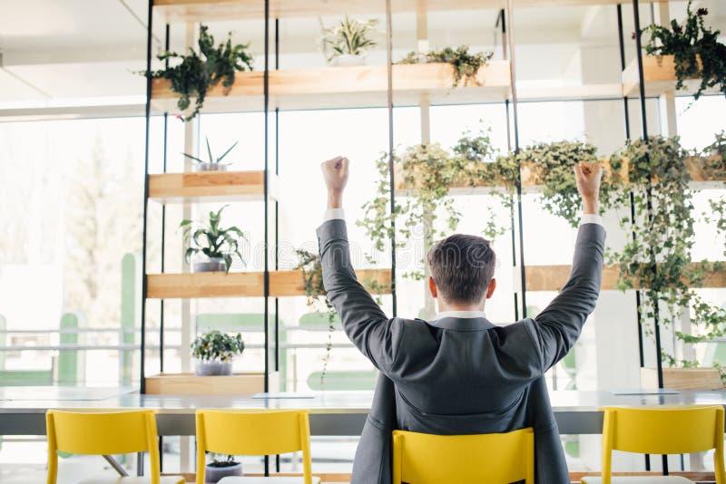 从后面,与被举的手胳膊的英俊的年轻商人的成功的激动的商人愉快的微笑举行拳头姿态视图 图库摄影