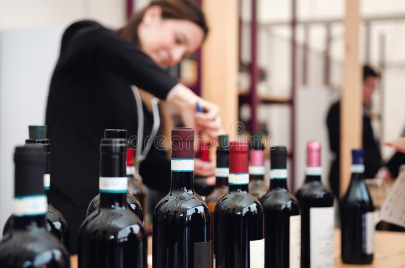 吐露一个瓶在山麓,意大利的红色dolcetto酒的女性斟酒服务员 图库摄影
