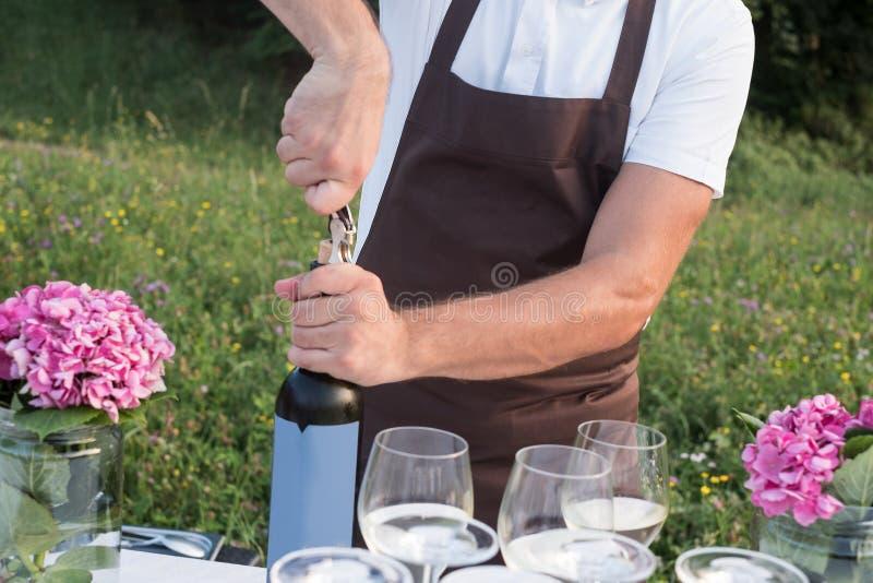 吐露一个瓶红葡萄酒的专业侍者在cele期间 免版税库存照片