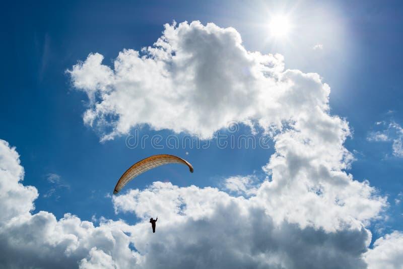 向上乘坐的悬挂式滑翔机到达云彩在太阳下 免版税库存照片