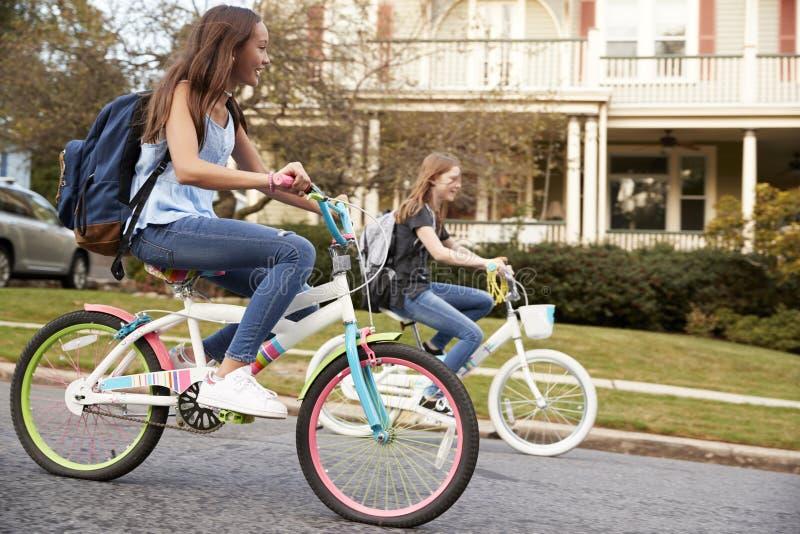 向上拱在街道,侧视图关闭的两个青少年的女孩自行车 图库摄影