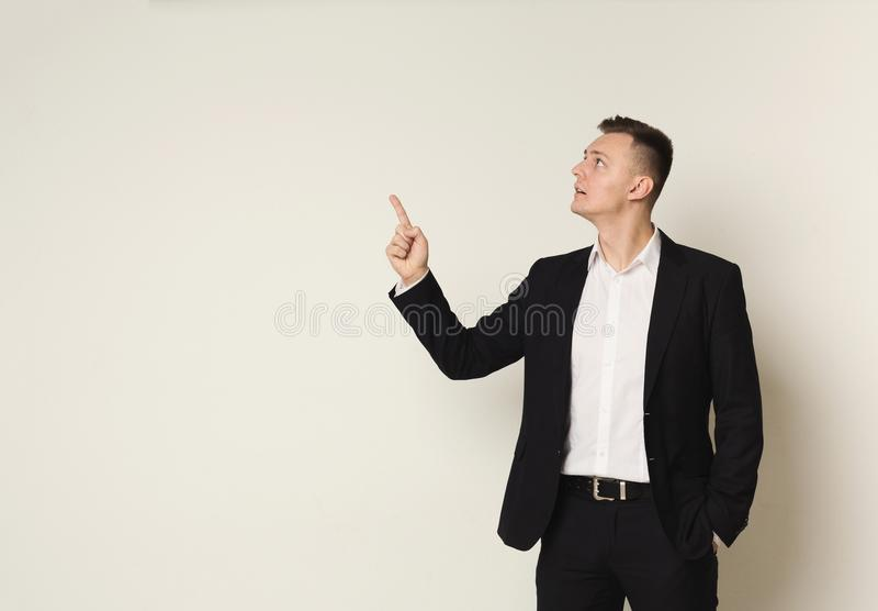 向上指向用手的年轻商人 免版税库存照片