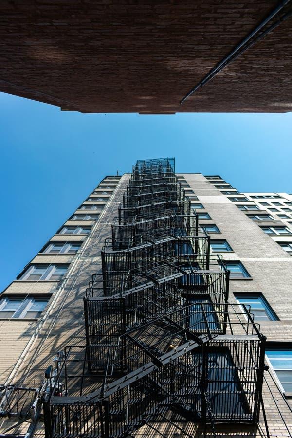 向上注视着在一个紧的胡同的防火梯在芝加哥 图库摄影