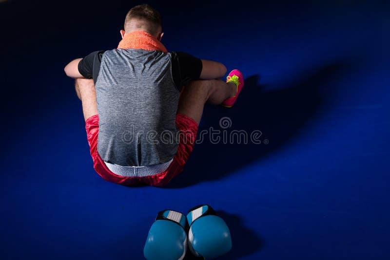 向后坐在拳击台的年轻运动男性拳击手 库存图片