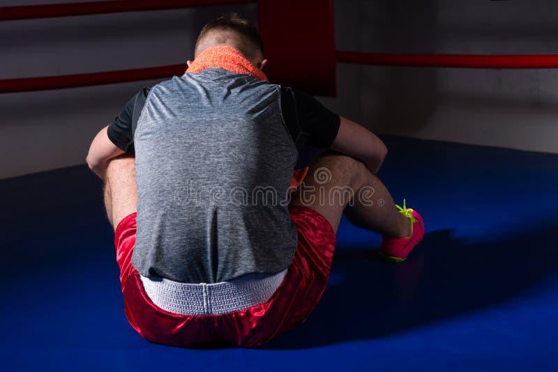 向后坐在规则拳击ri的年轻运动男性拳击手 免版税库存图片