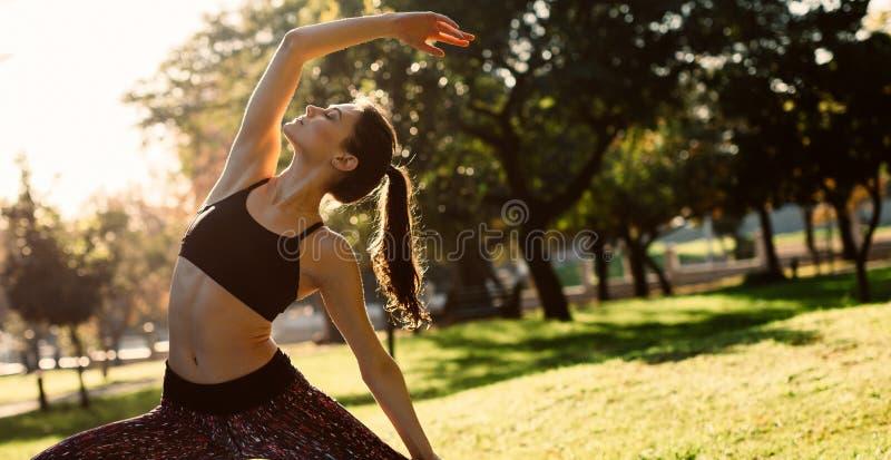 向后弯曲和舒展在公园的健康年轻女人 女性实践的舒展的瑜伽户外在早晨 库存照片