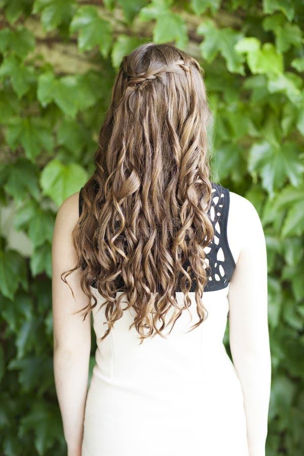 向后有瀑布辫子的长期卷曲的棕色头发看法  图库摄影