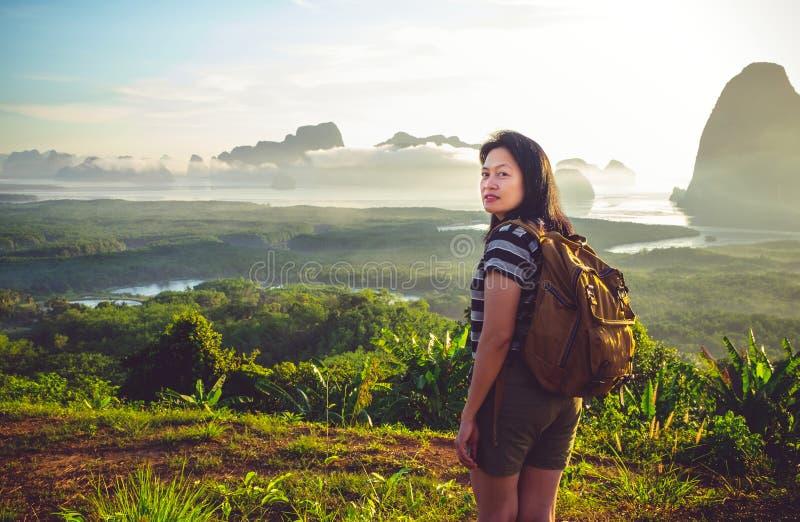 向后看对照相机的愉快的年轻旅客妇女背包徒步旅行者 库存照片