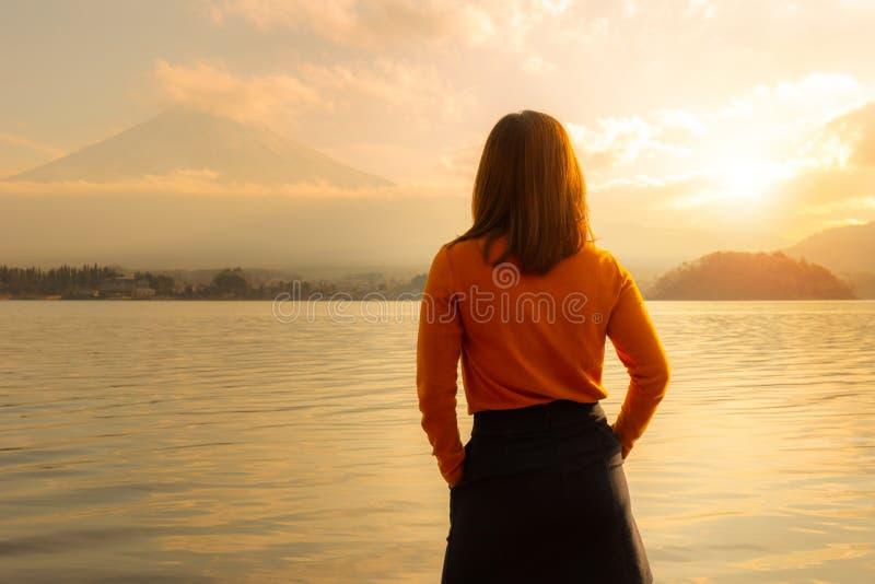 向后站立的年轻女人和观看的富士多山从湖川口边在日本国家 免版税库存照片