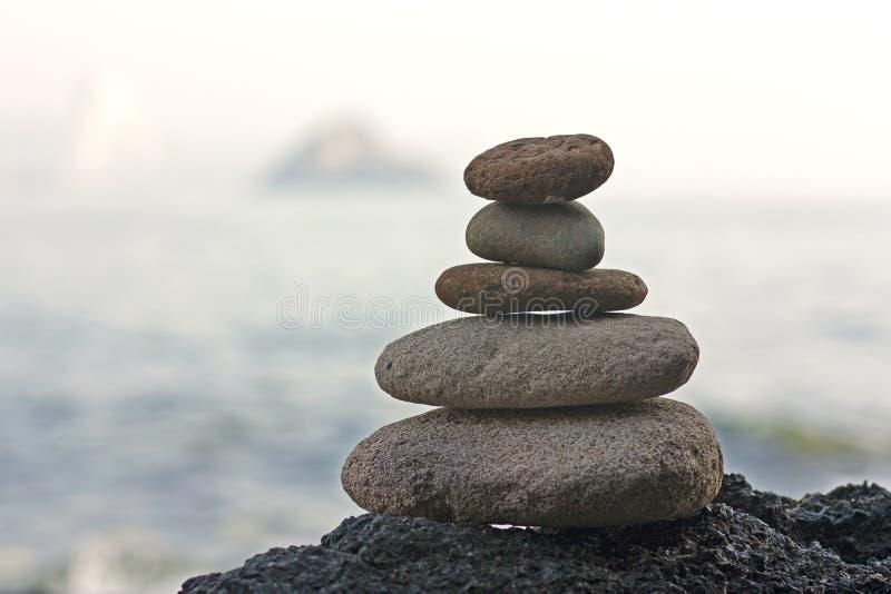 向在沙子象征的禅宗的金字塔扔石头 库存照片