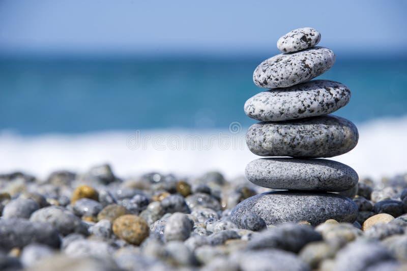 向在象征温泉概念有迷离海背景的Pebble海滩的金字塔扔石头 库存图片