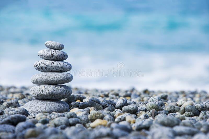 向在象征温泉概念有迷离海背景的Pebble海滩的金字塔扔石头 免版税库存图片