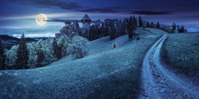 向堡垒废墟的道路在与森林的山坡在晚上 免版税库存图片