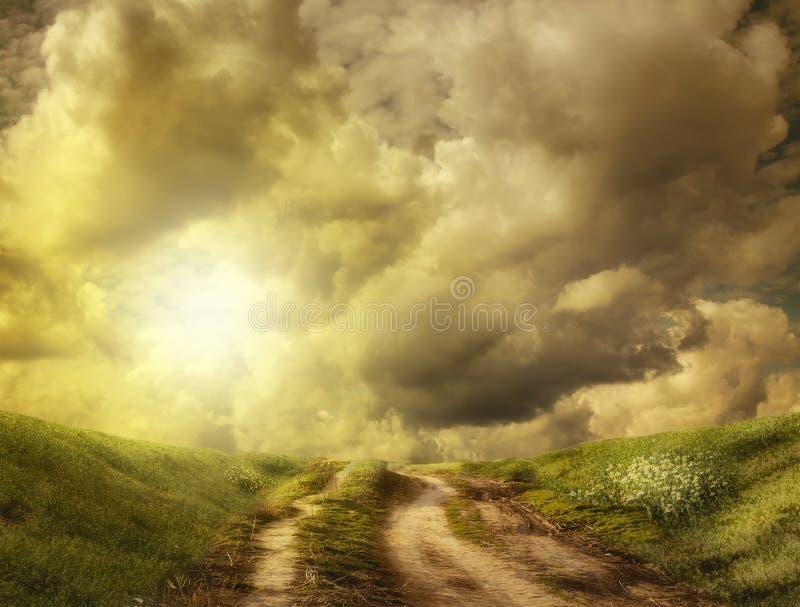 向小山的路在云彩 免版税库存照片