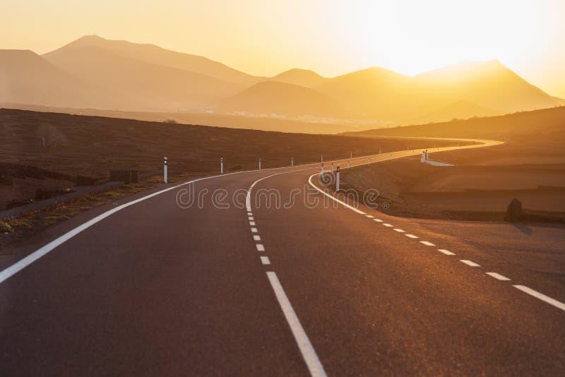 向山的柏油路在日落 免版税库存图片