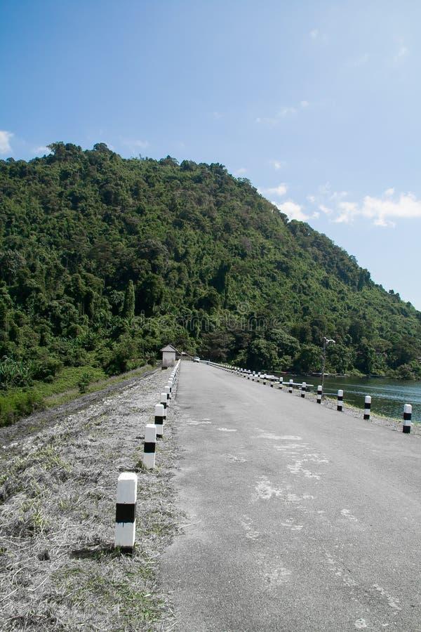 向山的漫长的路在水坝在泰国 免版税库存照片