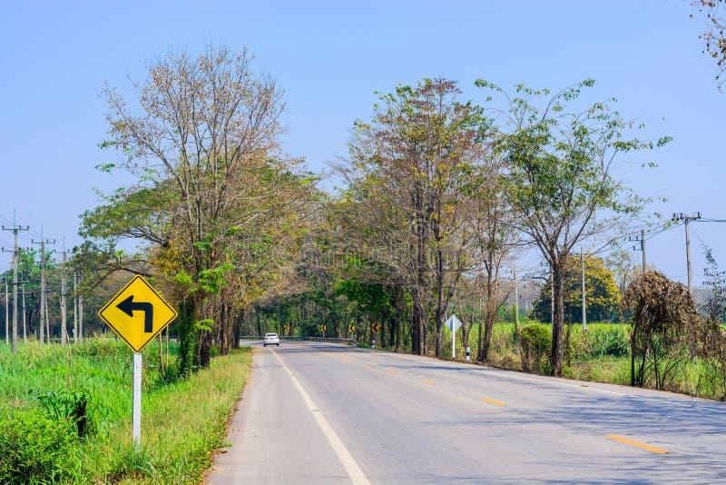 向左转在乡下公路的标志 免版税库存照片