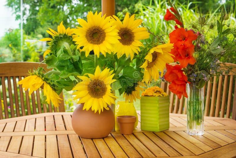 向日葵和剑兰在庭院桌上 库存图片